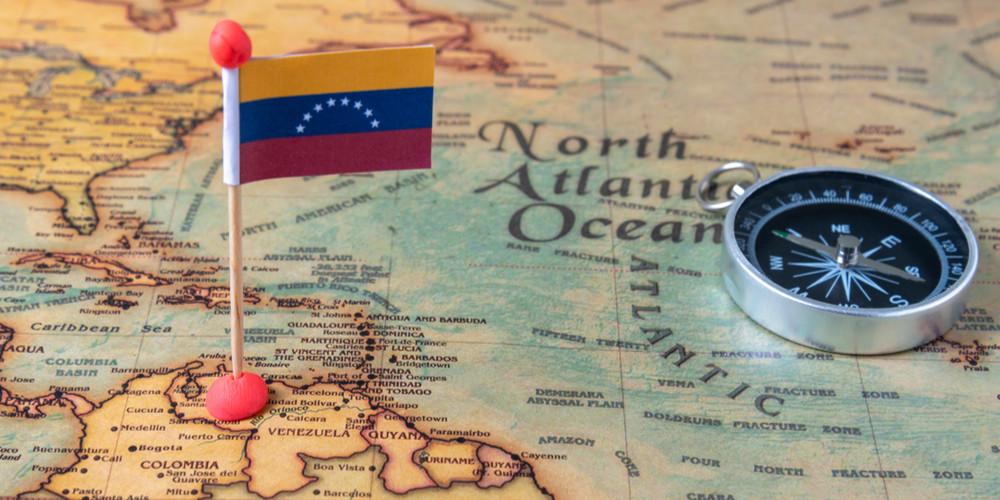 Флаг Венесуэлы и компас на карте мира